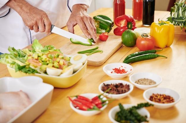 新鮮な野菜を切る男