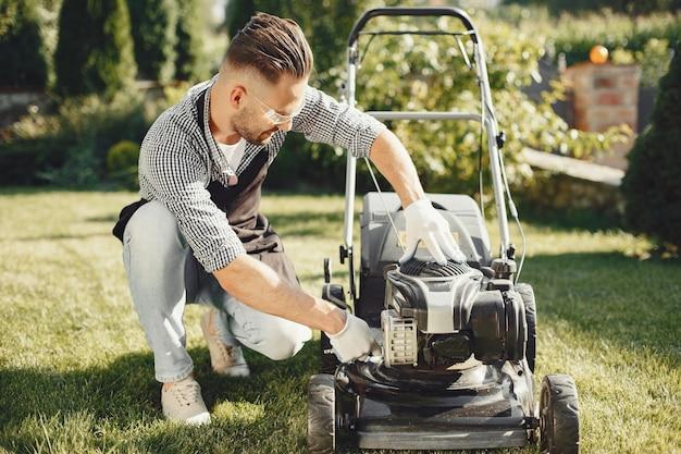 Uomo che taglia erba con prato mover nel cortile sul retro. maschio con un grembiule nero. guy ripara.