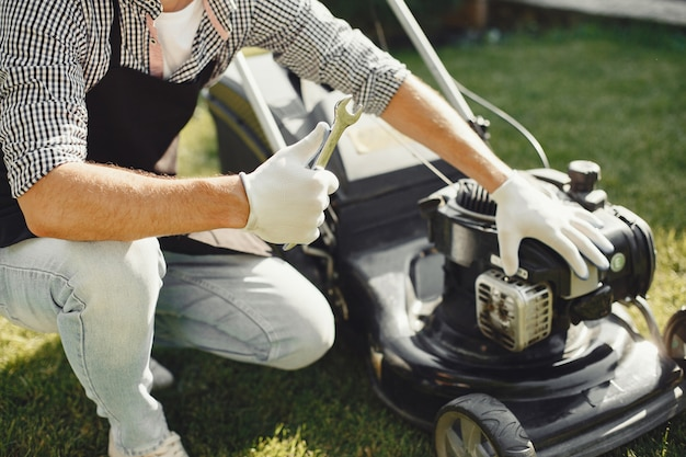 Man cutting grass with lawn mover in the back yard. male in a black apron. guy repairs.