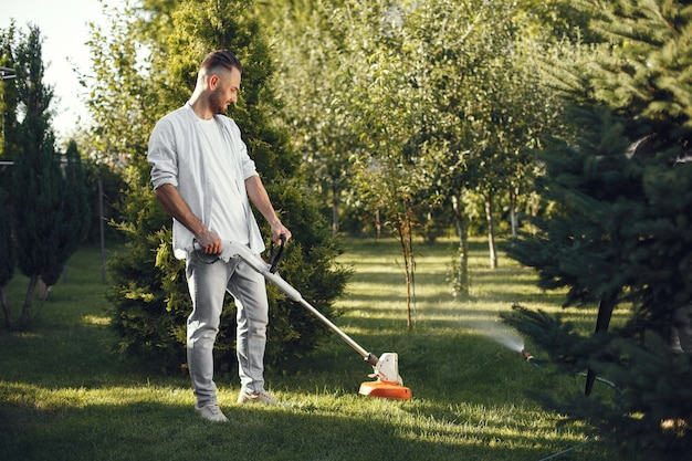 Uomo che taglia erba con prato mover nel cortile sul retro. maschio in una camicia.