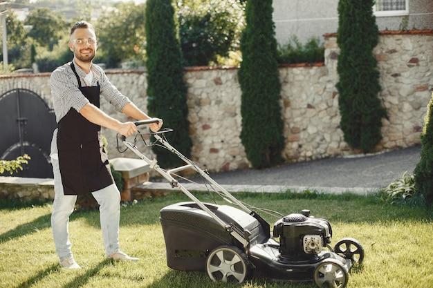 뒤뜰에 잔디 발동기와 잔디를 절단하는 사람. 검은 앞치마를 입은 남성.