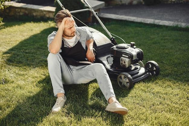 Мужчина косит траву газонокосилкой на заднем дворе. мужчина в черном фартуке.