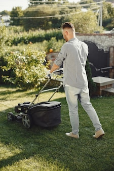 뒤뜰에 잔디 발동기와 잔디를 절단하는 사람. 셔츠에 남성.