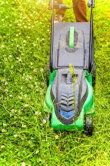 Человек режет зеленую траву с газонокосилкой на заднем дворе. садоводство фон образа жизни страны.