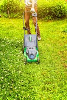 裏庭の芝刈り機で緑の草を刈る男
