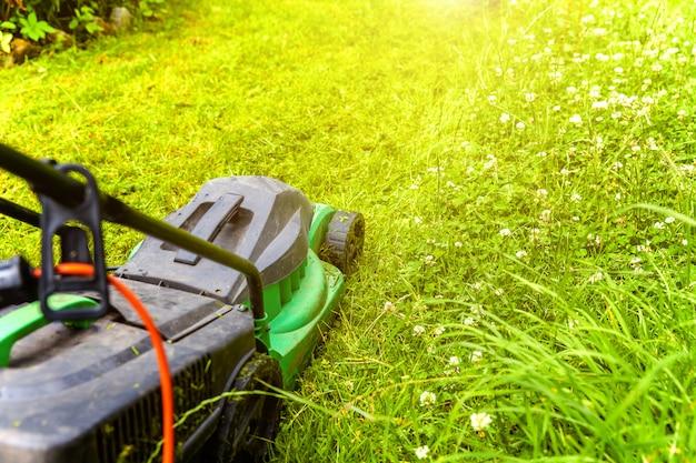 Человек резки зеленая трава с газонокосилка на заднем дворе. садоводство страны образ жизни фон.