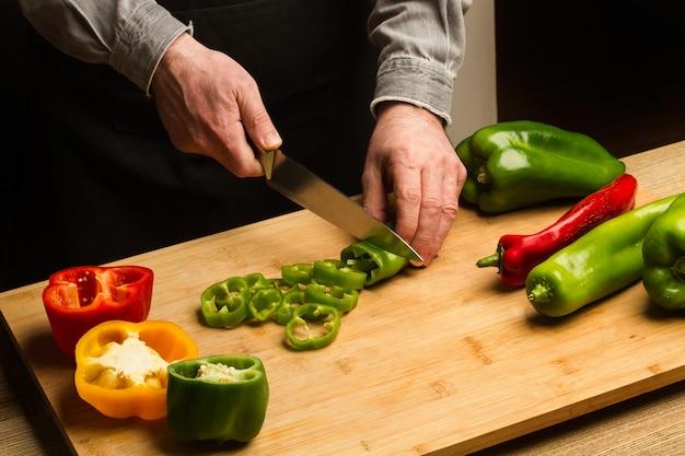 暗い背景の上の木製のキッチンボードで緑のイタリアのコショウを切る男