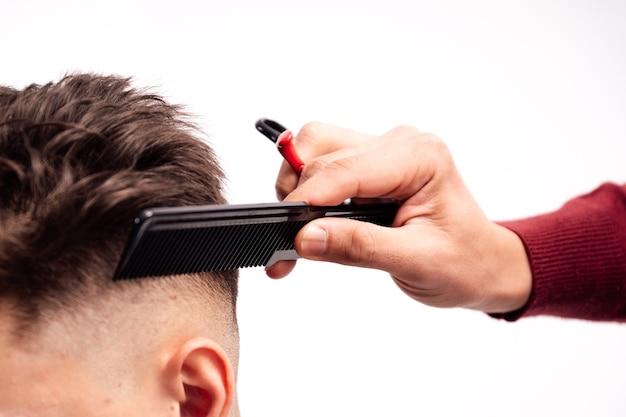 Man cutting hair on white background