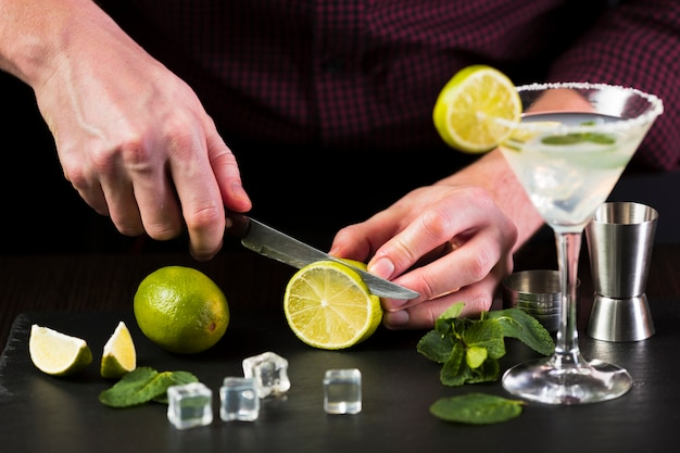 Man cutting lime for cocktail
