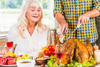 Man cutting roasted chicken at table near amazed woman