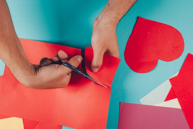 Man cutting shapes from colored papers on cyan blue