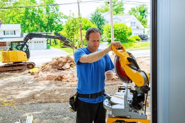 Man cutting shoe mouldingon electric saw