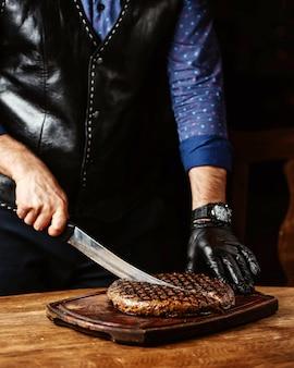 黒い手袋を身に着けている丸い形の男切削ステーキ