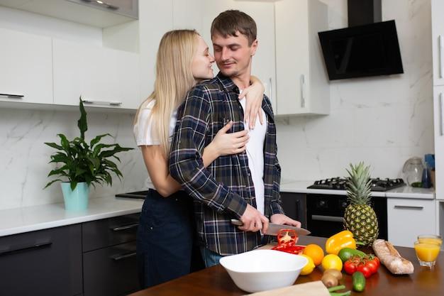 Мужчина режет овощной салат женщина обнимает мужчину сзади