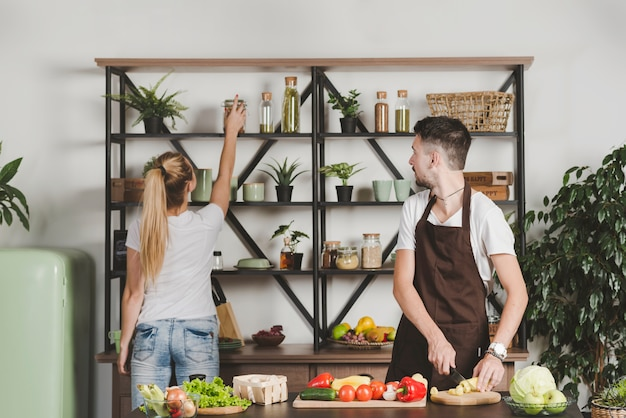 Man cutting vegetables looking at woman taking bottle from shelf