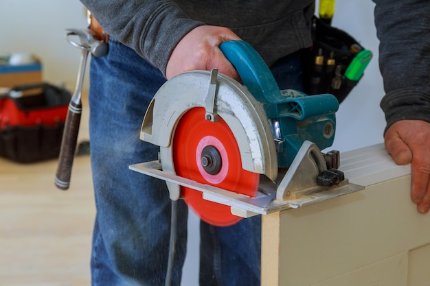 Man cutting wood door cuts circular saw the hands of the builder construction and home renovation