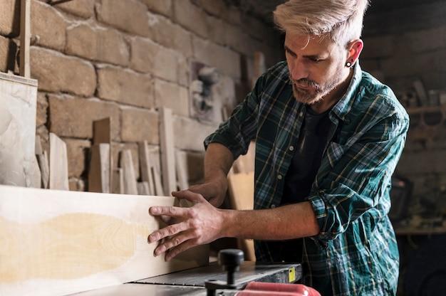 L'uomo il taglio di assi di legno
