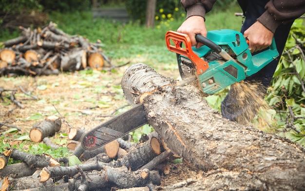 Мужчина режет дерево бензопилой.