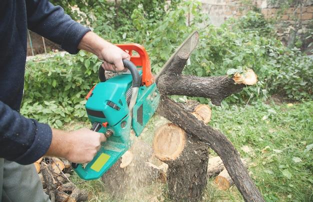 チェーンソーで木を切る男。