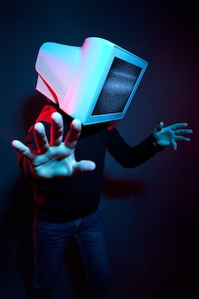 Man cyberpunk with a monitor instead of a head, computer addiction and zombie tv. zombification, tv on your head. the influence of tv on the brain, virtual reality