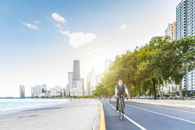 Man cycling in chicago with city
