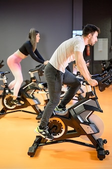 Man cycling on a modern fitness bicycle during group spinning class at the gym