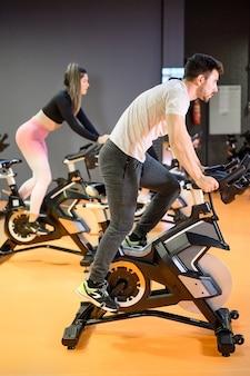 Мужчина катается на велосипеде на современном фитнес-велосипеде во время группового занятия спиннингом в тренажерном зале