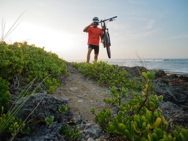 남자 자전거 타는 사람이 바다 해안에서 손에 자전거를 들고 있습니다. 바위 해변입니다.