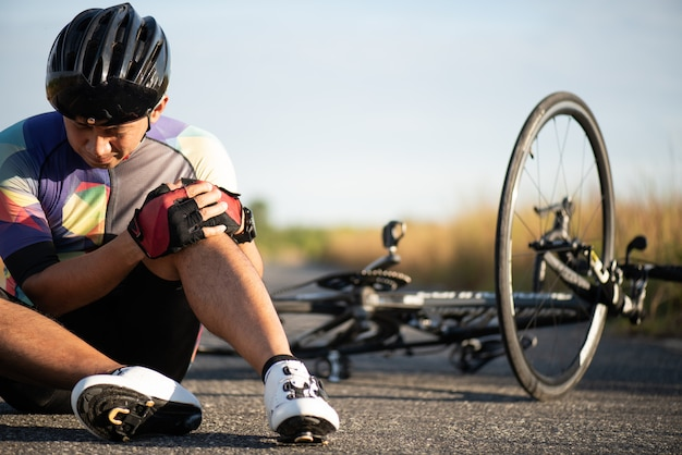 Man cyclist fell off road bike while cycling.