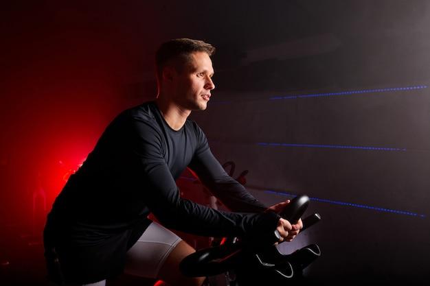 남자 사이클. 그는 어두운 공간에있는 체육관에서 혼자서 훈련을하고있다. 스포츠 및 심장 피트니스 개념