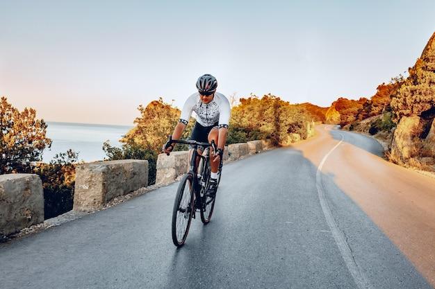 해안 도로에서 설정 태양 야외에서 도로 자전거에 페달을 밟는 남자 사이클