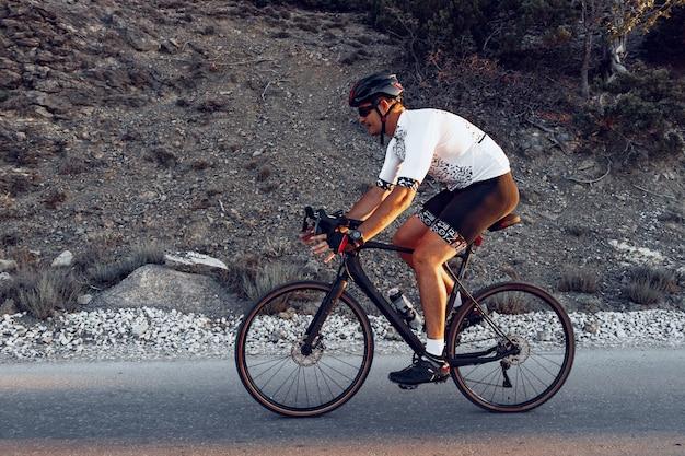 屋外のロードバイクでペダルを踏んでいる男性サイクリスト