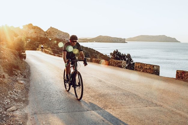 Man cyclist pedaling on a road bike outdoors in sun set at coastal road