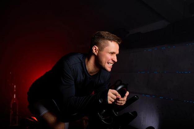 남자 사이클 선수는 이빨을 긁적이며 어두운 공간에서 체육관에서 운동하고 혼자 훈련하고 있습니다. 스포츠 및 심장 피트니스 개념