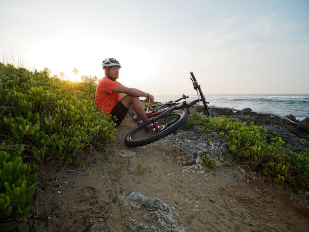 바다 해안선에서 산악 자전거와 함께 흰색 헬멧과 오렌지색 티셔츠를 입은 남자 자전거 타는 사람. 바위 해변입니다.