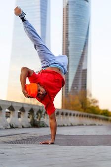 Человек танцует брейк-данс в городе