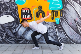 Man dancing in front of painted wall