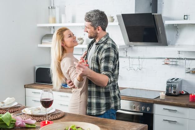 Мужчина танцует с улыбающейся женщиной возле стола на кухне