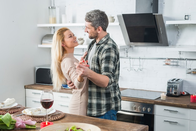 Man dancing with smiling woman near table in kitchen
