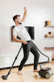 Man dancing with vacuum cleaner long shot