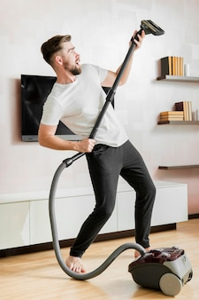 Man dancing with vacuum cleaner