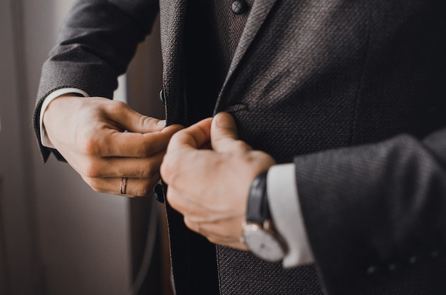 A man in a dark business suit buttoning a button on his jacket.