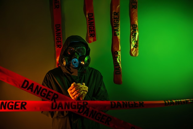 A man in a dark green protective suit with a gas mask on his face and a hood on his head posing standing near a green wall with hanging danger tapes. danger concept