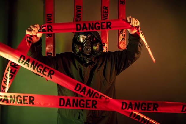 A man in a dark protective suit with a gas mask on his face and a hood on his head posing standing near a green wall holding danger tapes over his headdanger