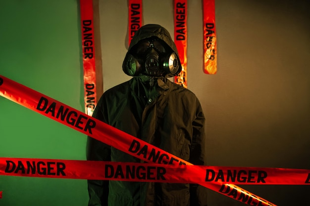 A man in a dark protective suit with a gas mask on his face and a hood on his head posing standing near a green wall with a cross from danger tapes. danger concept