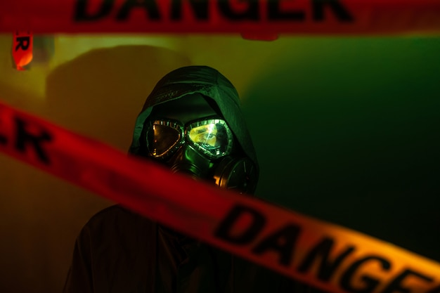 A man in a dark protective suit with a gas mask on his face and a hood on his head posing standing near a green wall with danger tapesdanger