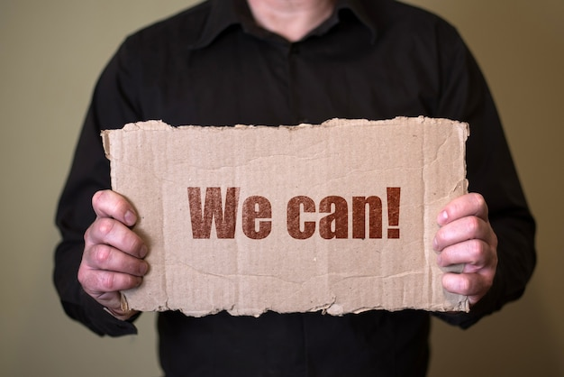 A man in a dark shirt holding a piece of cardboard with text we can.