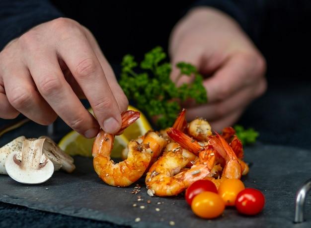 男は石のトレイに野菜と揚げたエビの料理を飾る