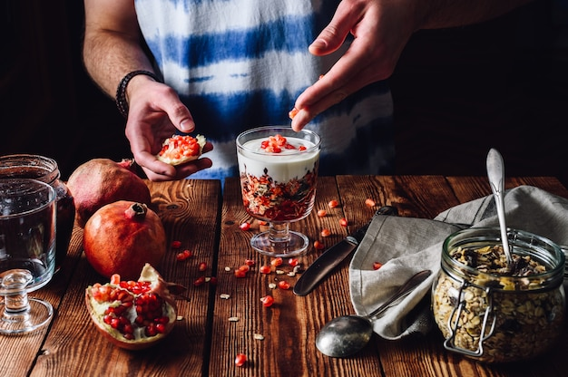 Man decorates dessert with pomegranate seeds.