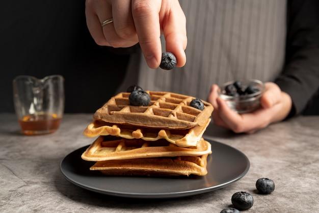 Человек украшает стопку вафель с черникой